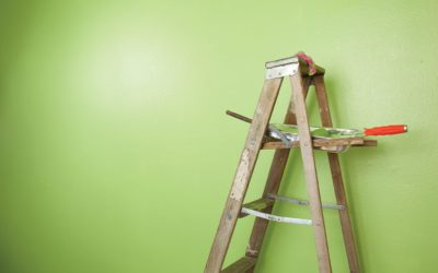 Old antique wooden ladder stands against a half painted green wall with paint roller and tray