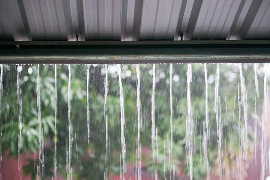 雨水流从波纹屋顶倾泻而下