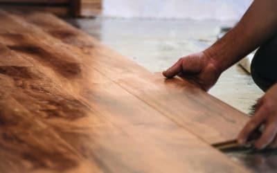 Man installing wood flooring in home