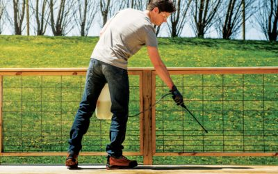 man spraying wood deck with preservative