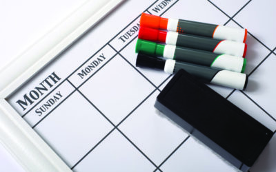 Blank white calendar with dry erase markers and an eraser