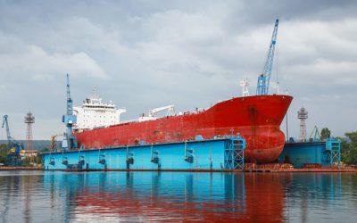 Big red tanker under repairing in blue floating dock