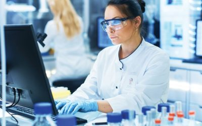 Medical Research Scientist Typing Information Obtained from New Experimental Drug Trial. She Works in a Bright and Modern Laboratory.