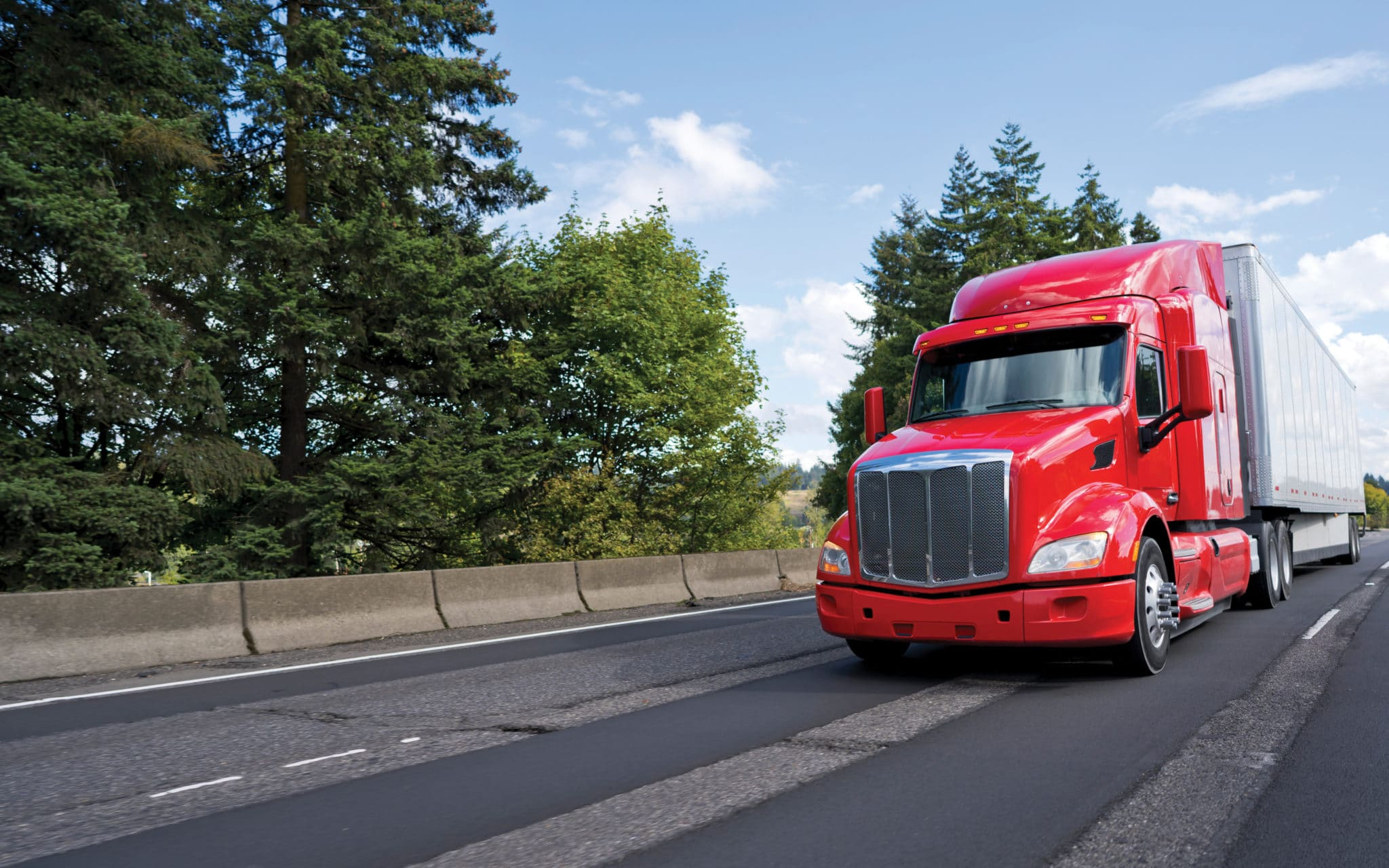 Bright modern long haul big rig semi truck with semi trailer moving on the green road