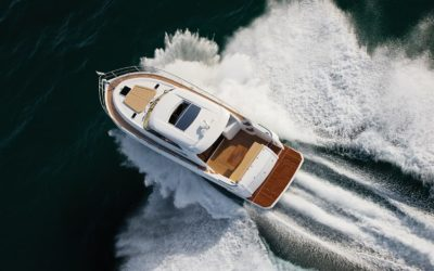 Small yacht sailing at very high speed and splashing water to all sides