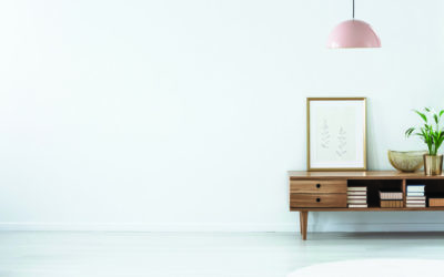 Retro pink ceiling lamp above a wooden sideboard in a modern living room interior