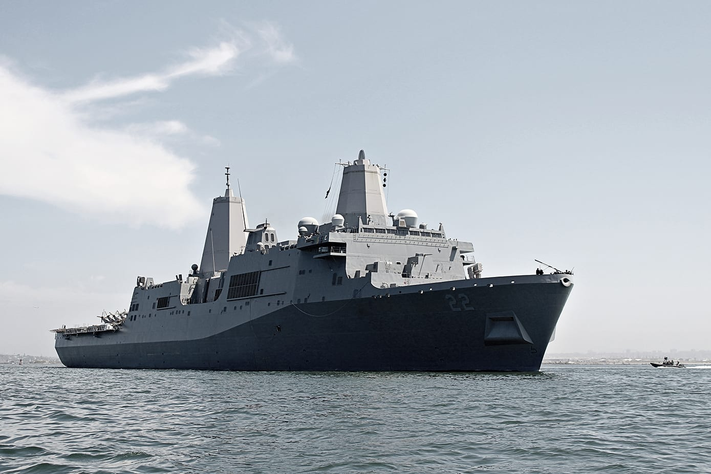 The USS Somerset (LPD-25) looms over a Naval Special Warfare boat in the San Diego Bay.