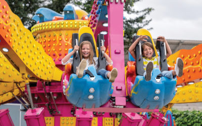 Happy kids having fun in an amusement park riding on a fun ride and screaming - lifestyle concepts