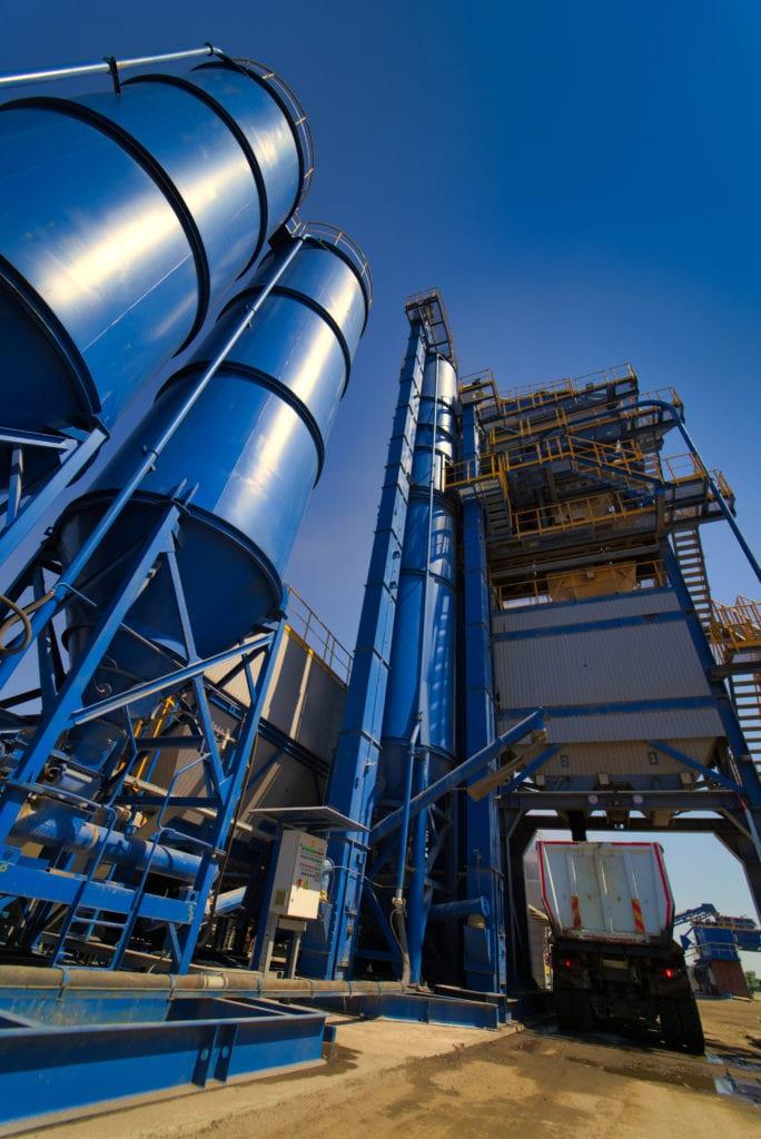 生产沥青、水泥和混凝土的设备。 混凝土厂。 沥青厂的高塔。 有害生产。 沥青和砾石的混合物,混合机。