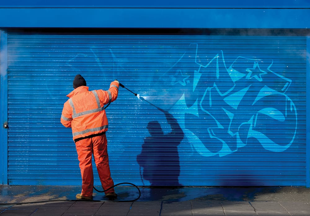 Washing graffiti off a security grill.