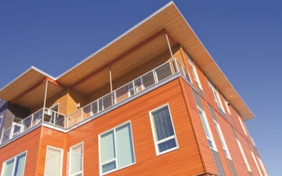 Upper storey detail of timber clad apartment building painted bright with penthouse balcony under blue sky