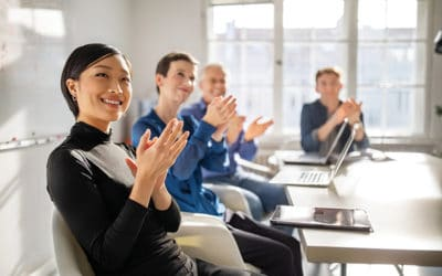 Business professionals clapping hands in a meeting