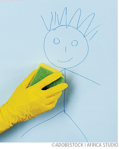 rubber glove wiping away a child's drawing on wall