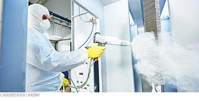 coatings specialist spraying white powder coating