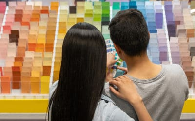 Couple at hardware store choosing a color for their house project